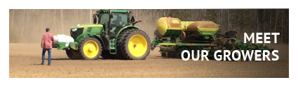 Meet our growers. Farmer with John Deere green tractor and equipment
